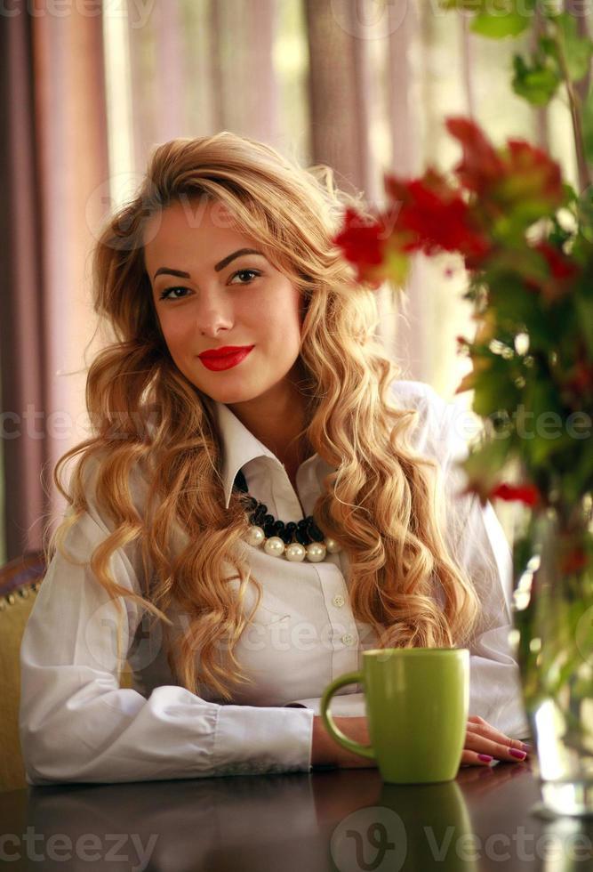 linda mulher sorridente sentada em casa com uma xícara de café foto