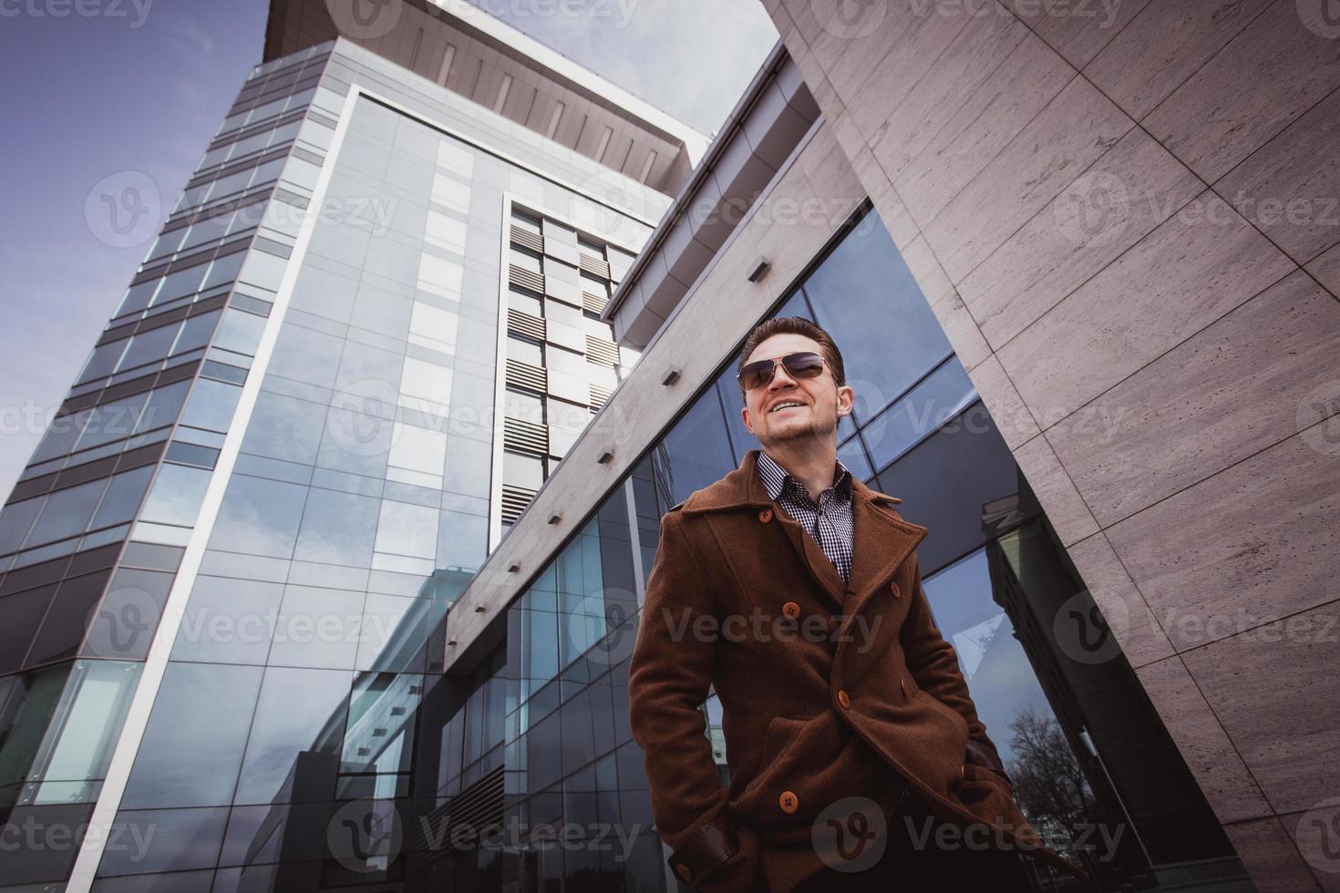 homem da moda em frente a um prédio de vidro foto
