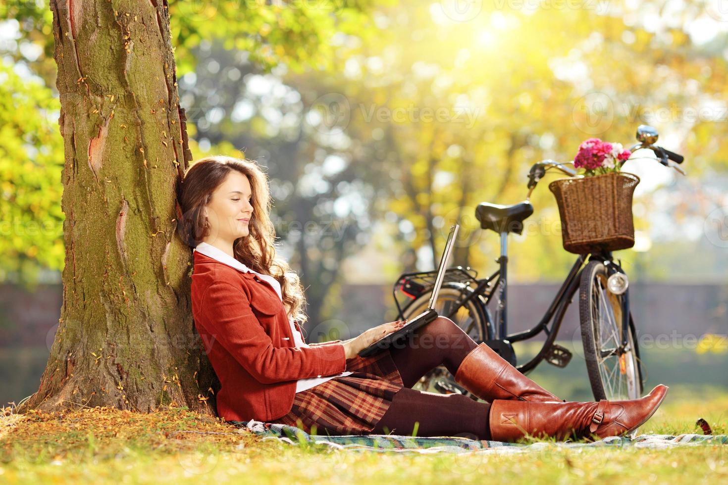 mulher relaxada trabalhando em um laptop em um parque foto