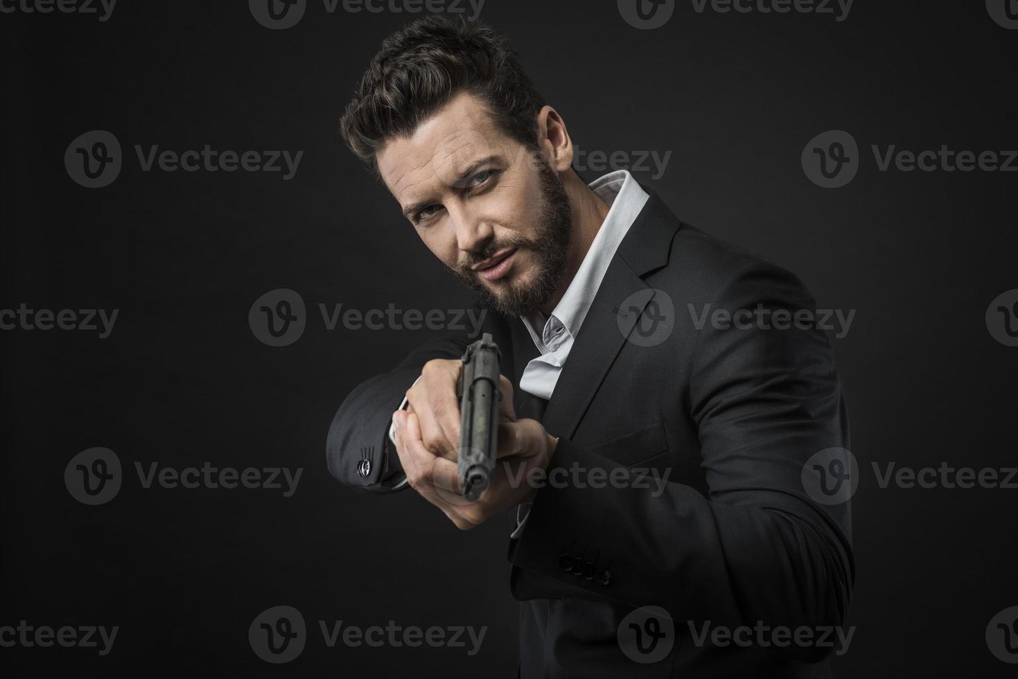 homem bonito legal apontando uma arma foto