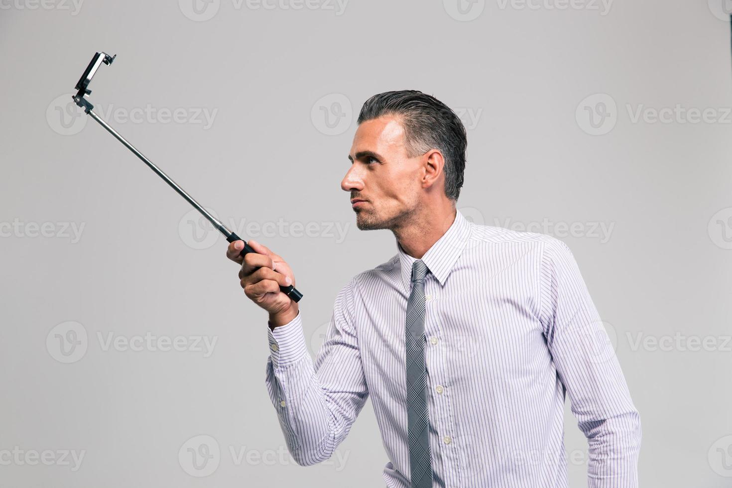 empresário bonito segurando uma vara de selfie foto