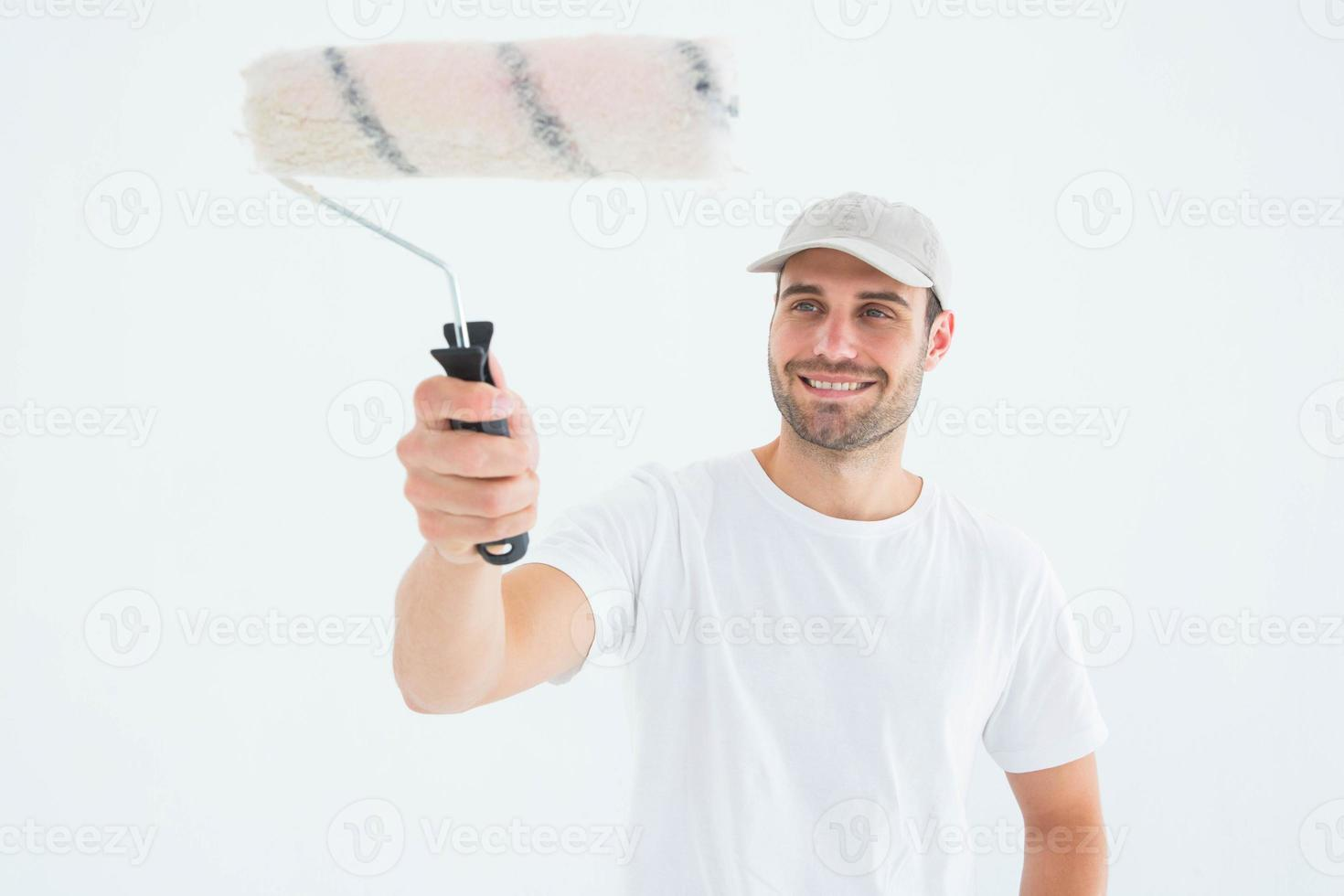 homem feliz usando rolo de pintura foto