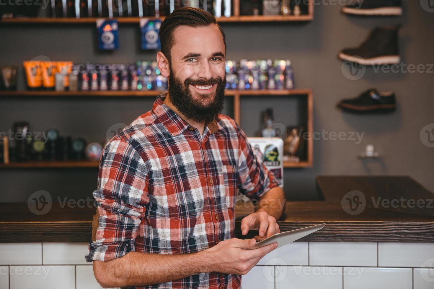 homem bonito e feliz com barba usando tablet na barbearia foto