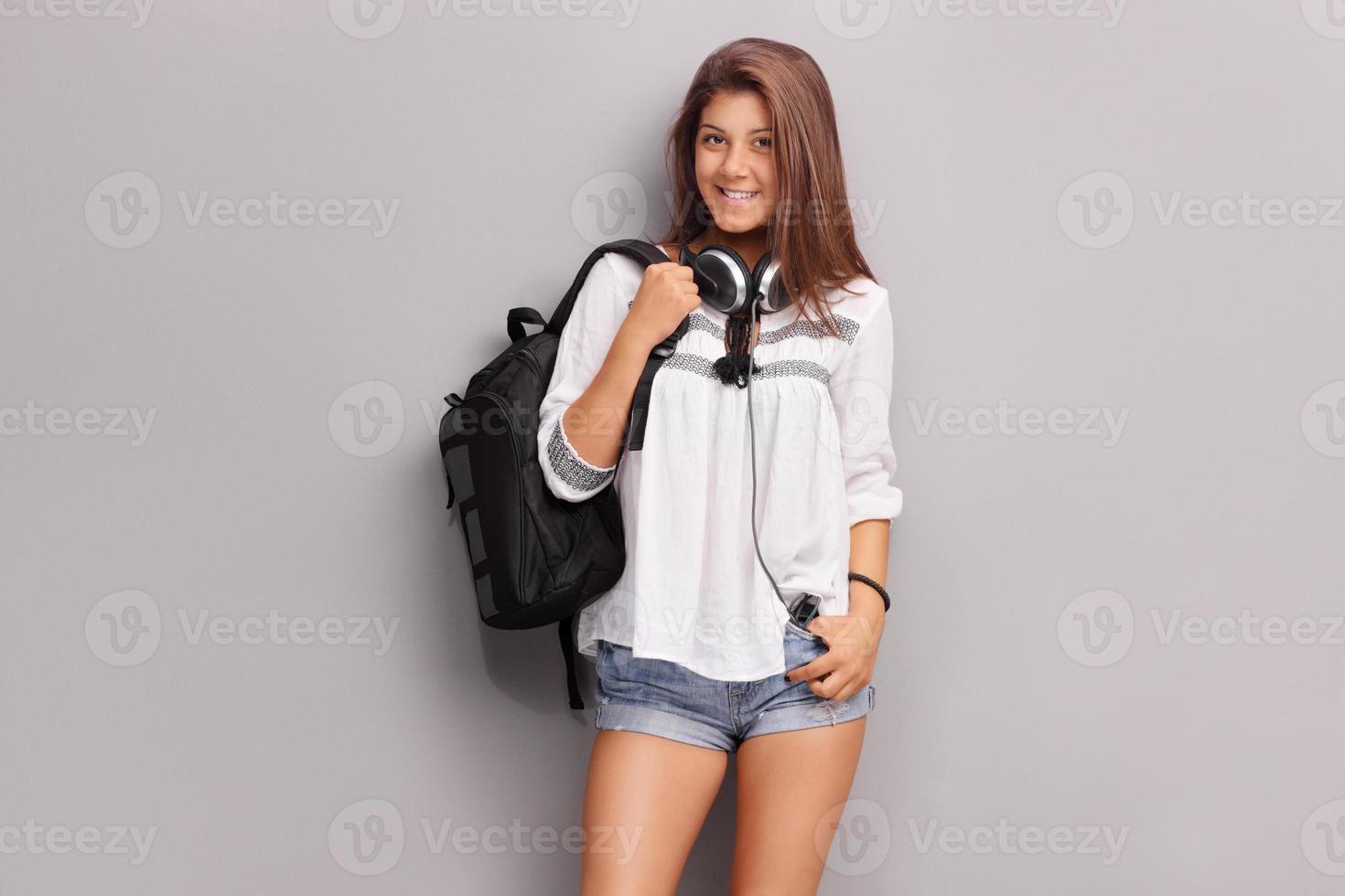 adolescente com fones de ouvido carregando uma mochila foto