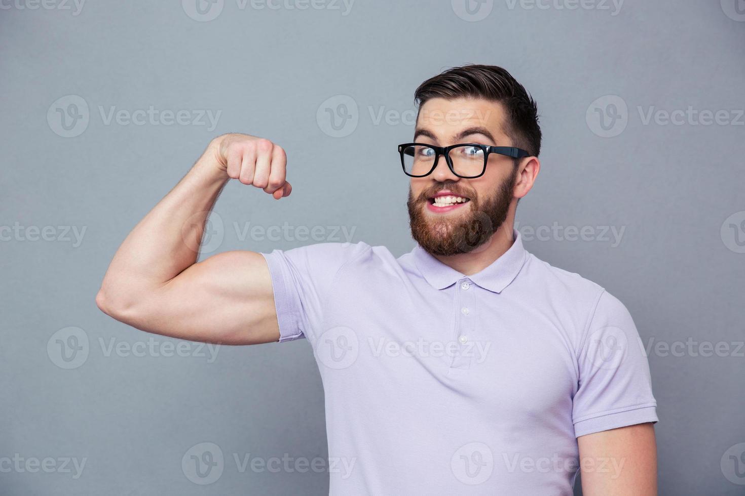 homem engraçado de óculos mostrando seus músculos foto