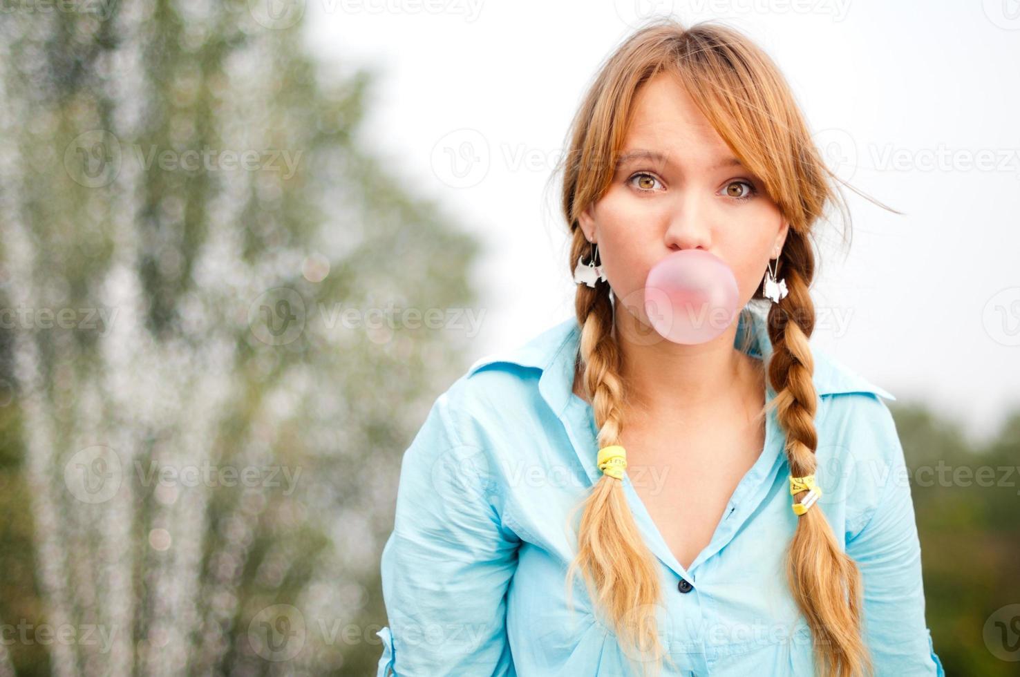 jovem estudante ruiva com tranças trançadas soprando chiclete foto