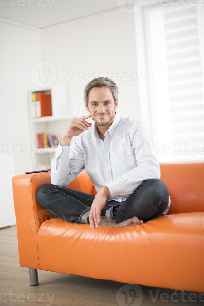 homem atraente, sorrindo em um sofá foto