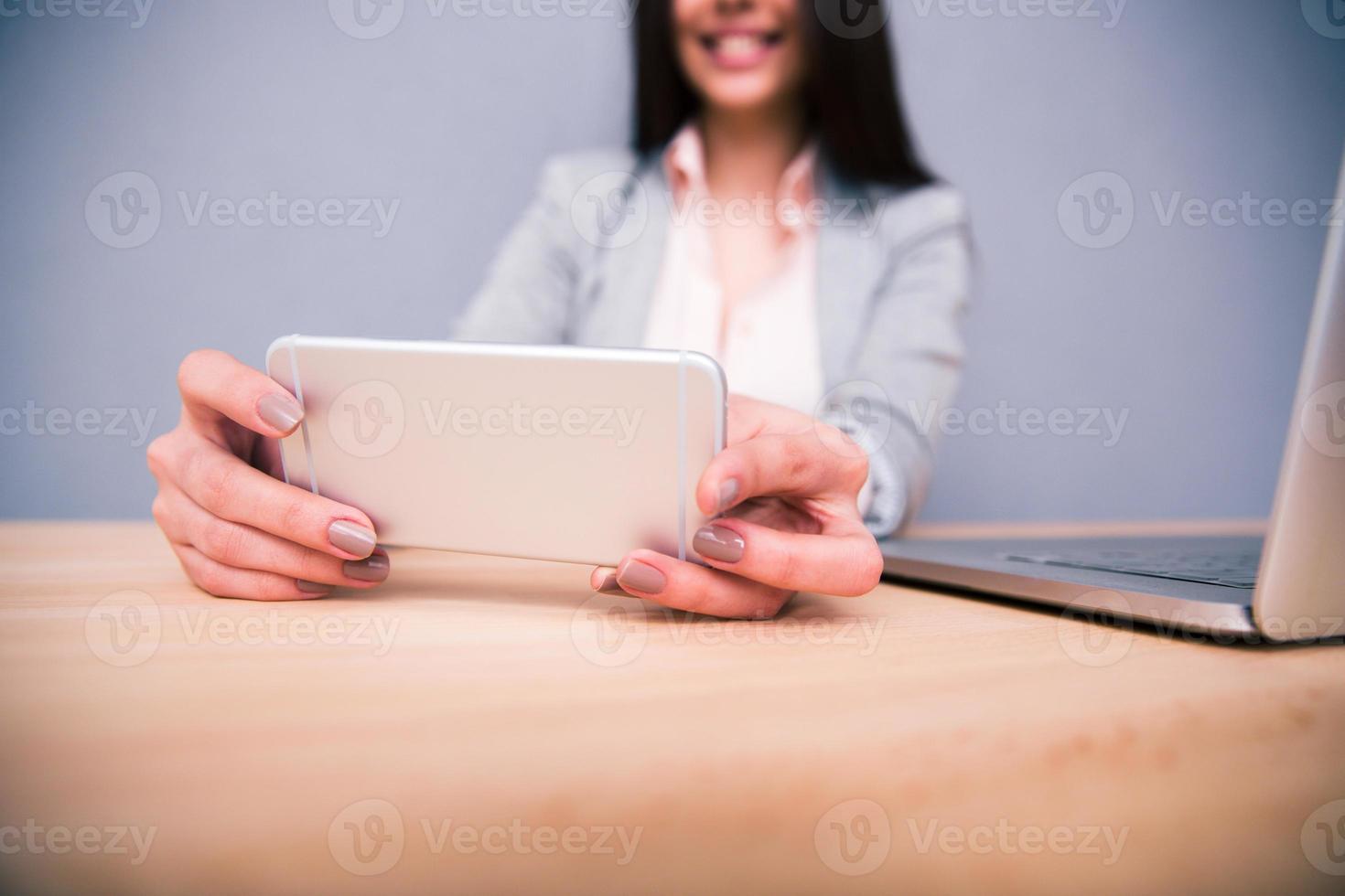 empresária sentada à mesa com smartphone foto