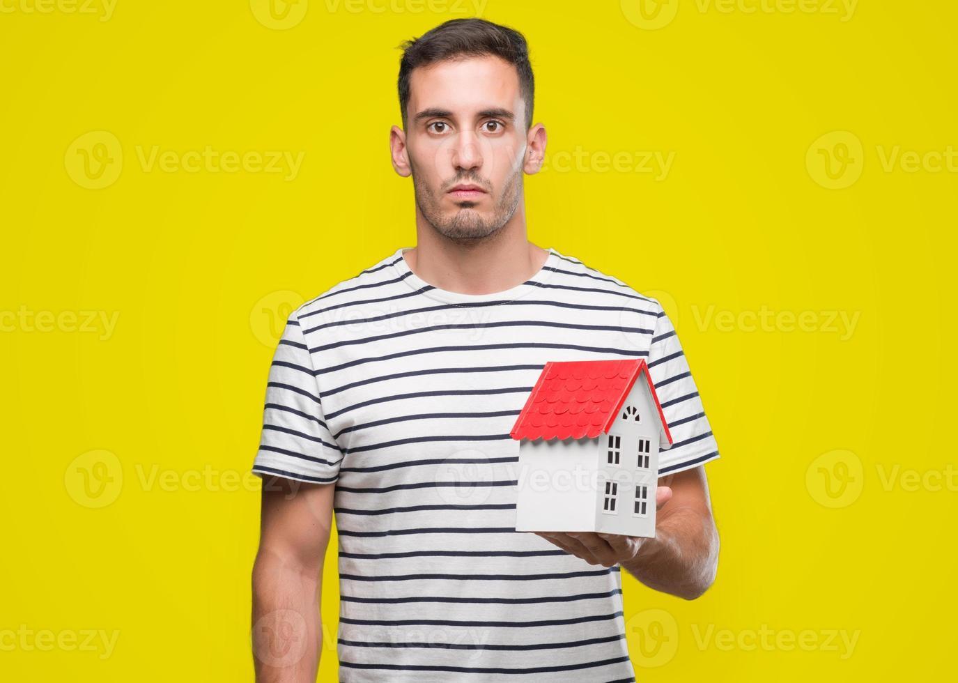 belo agente imobiliário segurando uma casa com uma expressão confiante no rosto inteligente pensando sério foto