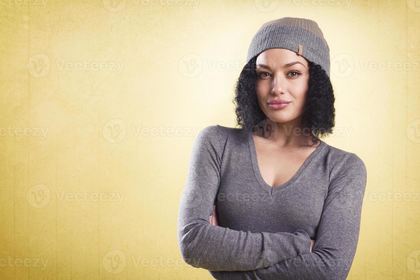 menina na moda com os braços cruzados, isolados no fundo amarelo. foto