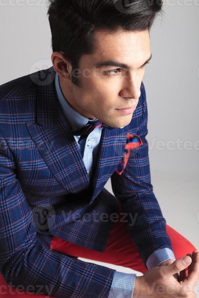 homem da moda jovem sentado olhando para longe. foto