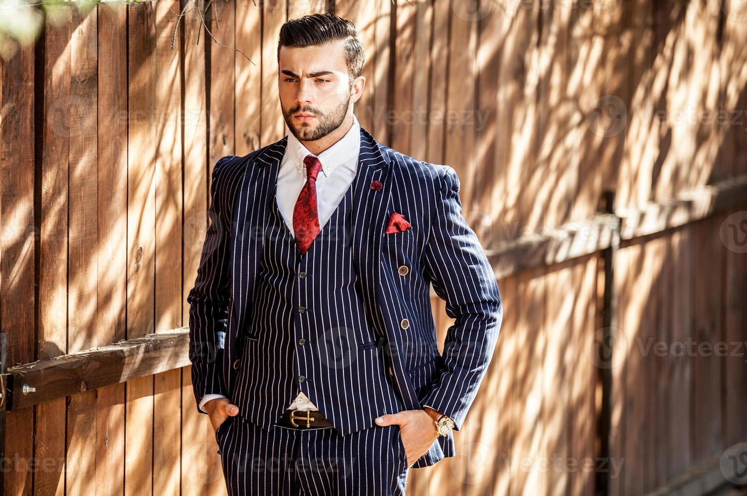 homem contra uma cerca de madeira em um terno elegante. foto