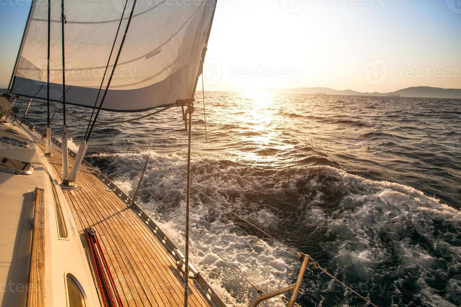 iates de luxo. iate navegando em direção ao pôr do sol. foto