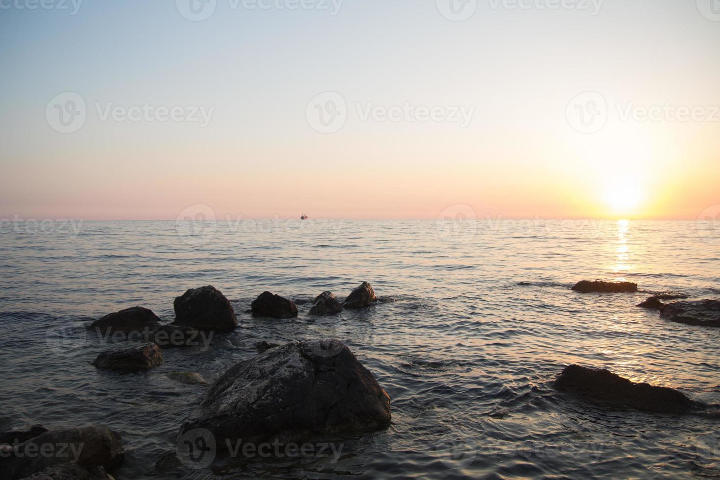 pôr do sol sobre o mar entre as rochas foto