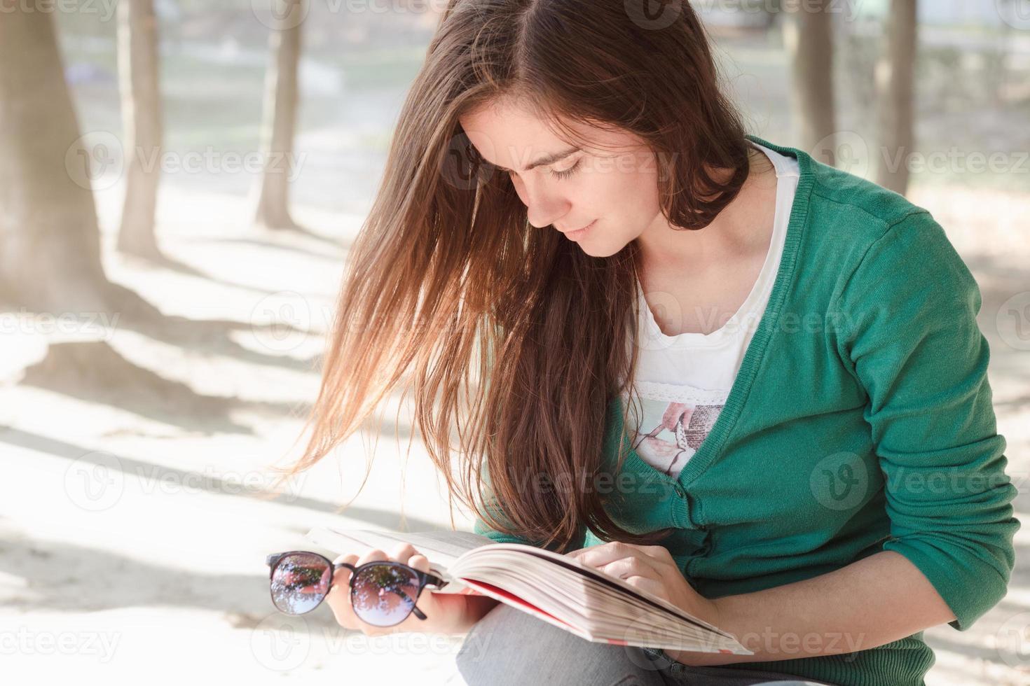 mulher lendo um livro no parque perto do lago foto