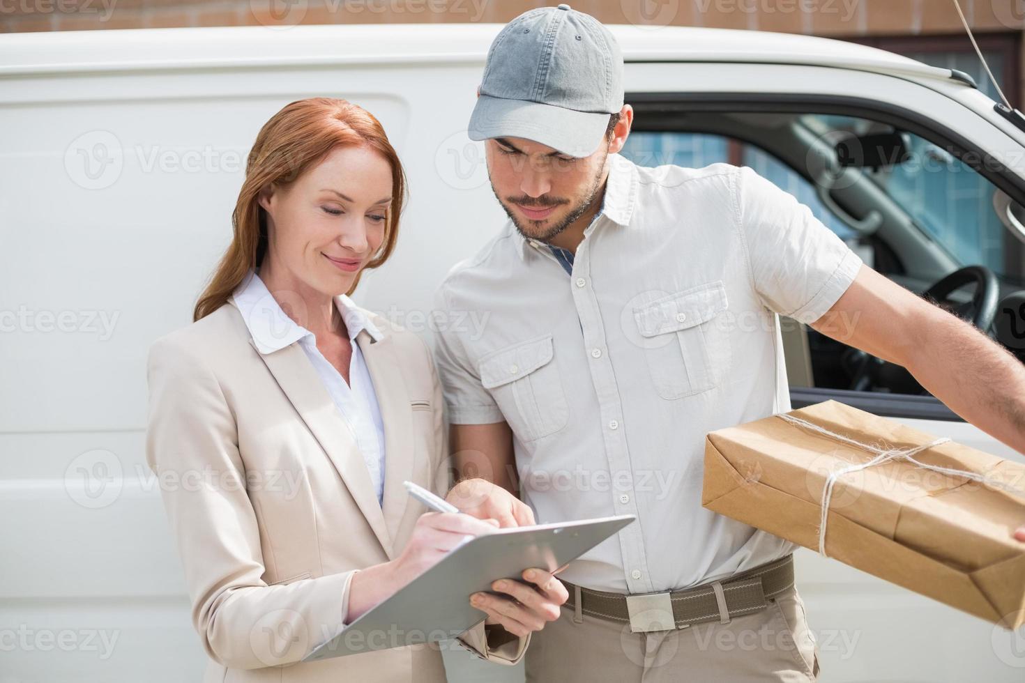 motorista de entrega mostrando onde assinar com o cliente foto