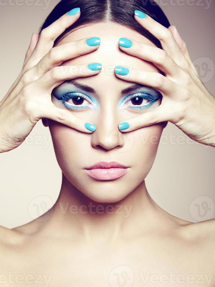jovem bonita com maquiagem brilhante e manicure foto