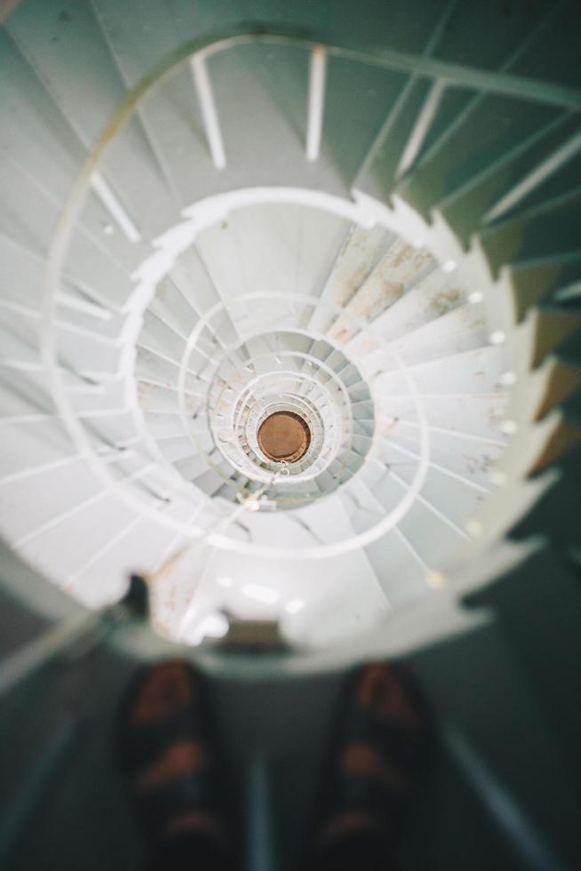 pessoa em pé na escada em espiral foto