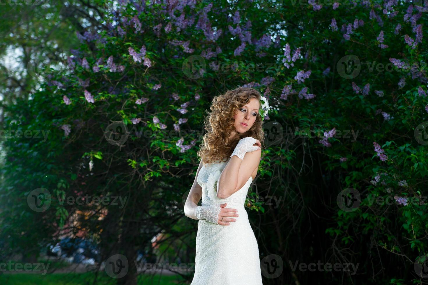 linda noiva em um vestido branco sobre fundo lilás foto
