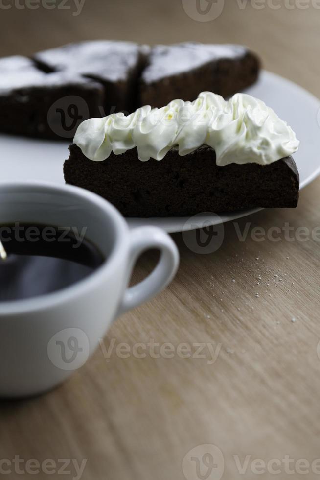 fatia de bolo de chocolate com café preto foto