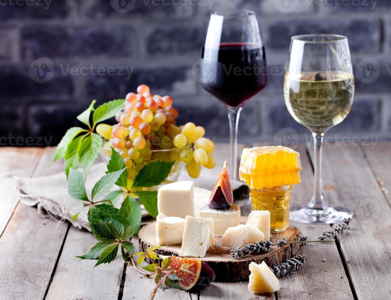 prato de queijo com mel, uva, vinho em taças foto