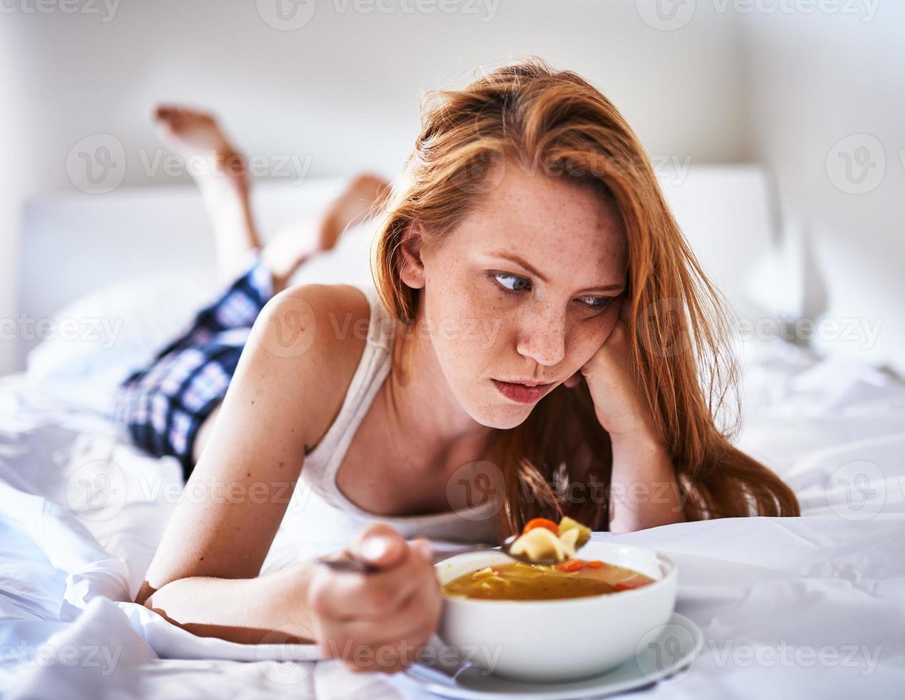 na cama comendo sopa de macarrão de galinha enquanto estava doente foto