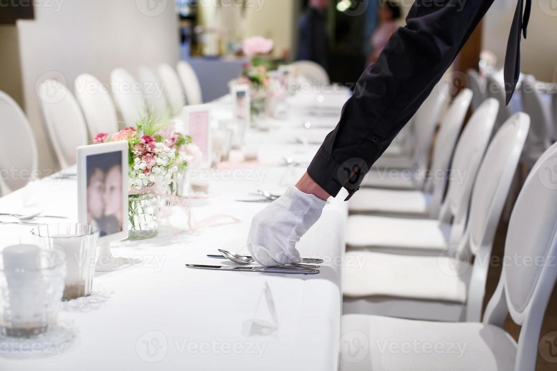 homem cobrindo a mesa com talheres para casamento foto