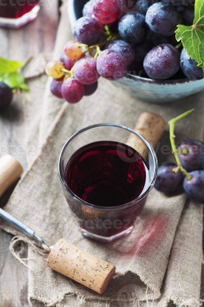 vinho tinto e uva na mesa de madeira foto