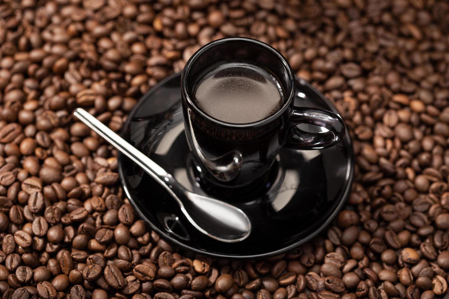café expresso em xícara preta e grãos torrados foto