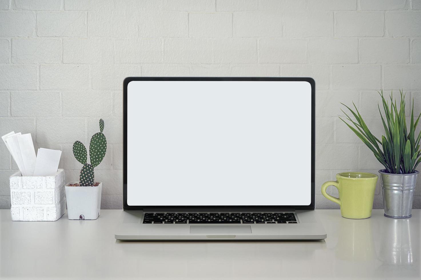 maquete de laptop com plantas em uma mesa foto