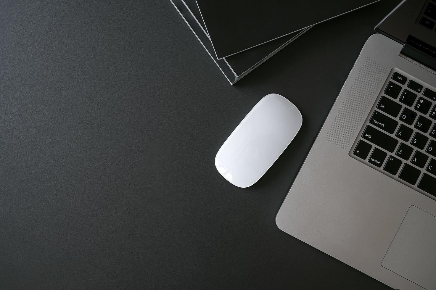 laptop, mouse e livros em uma mesa preta foto