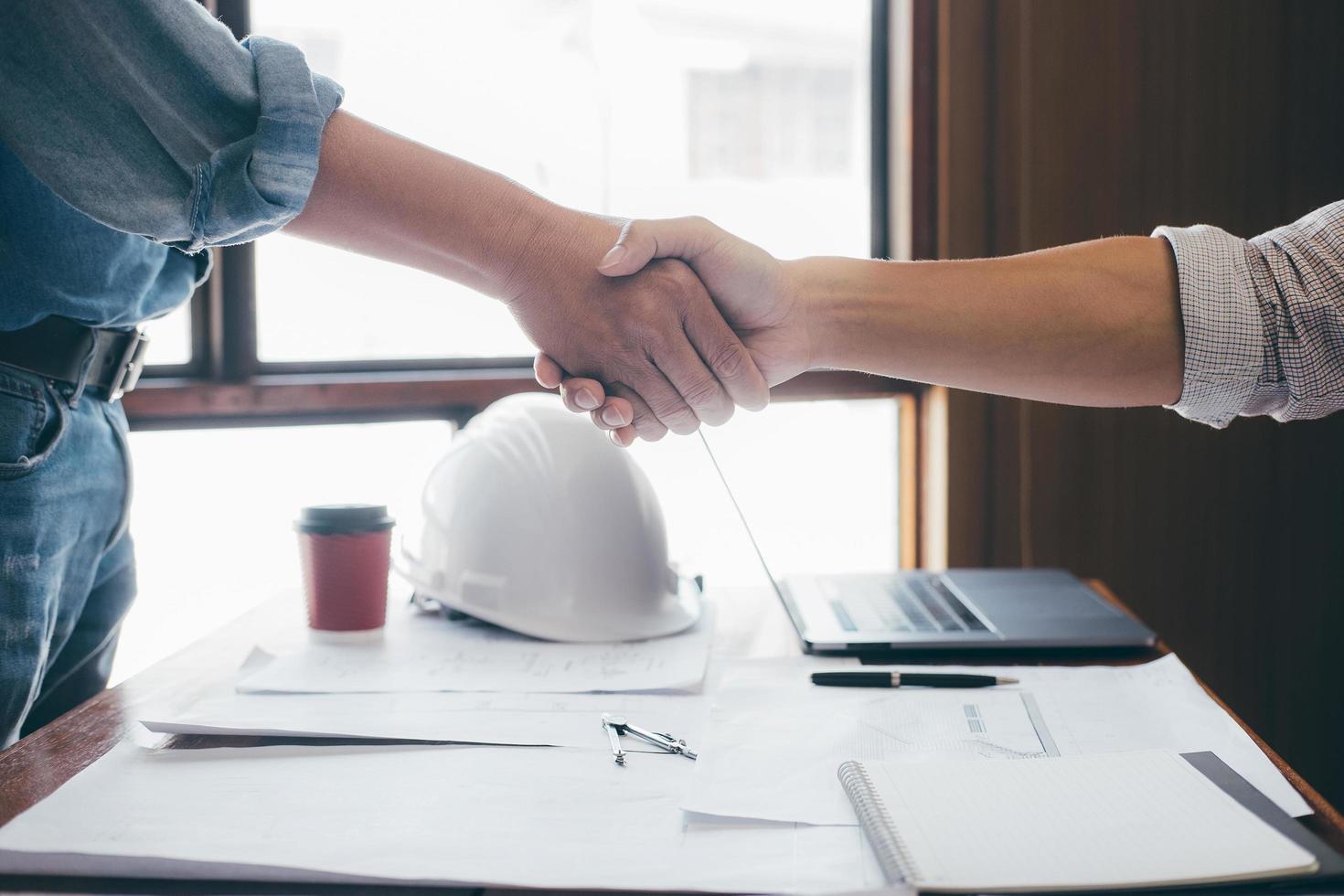 close-up de dois engenheiros apertando as mãos foto