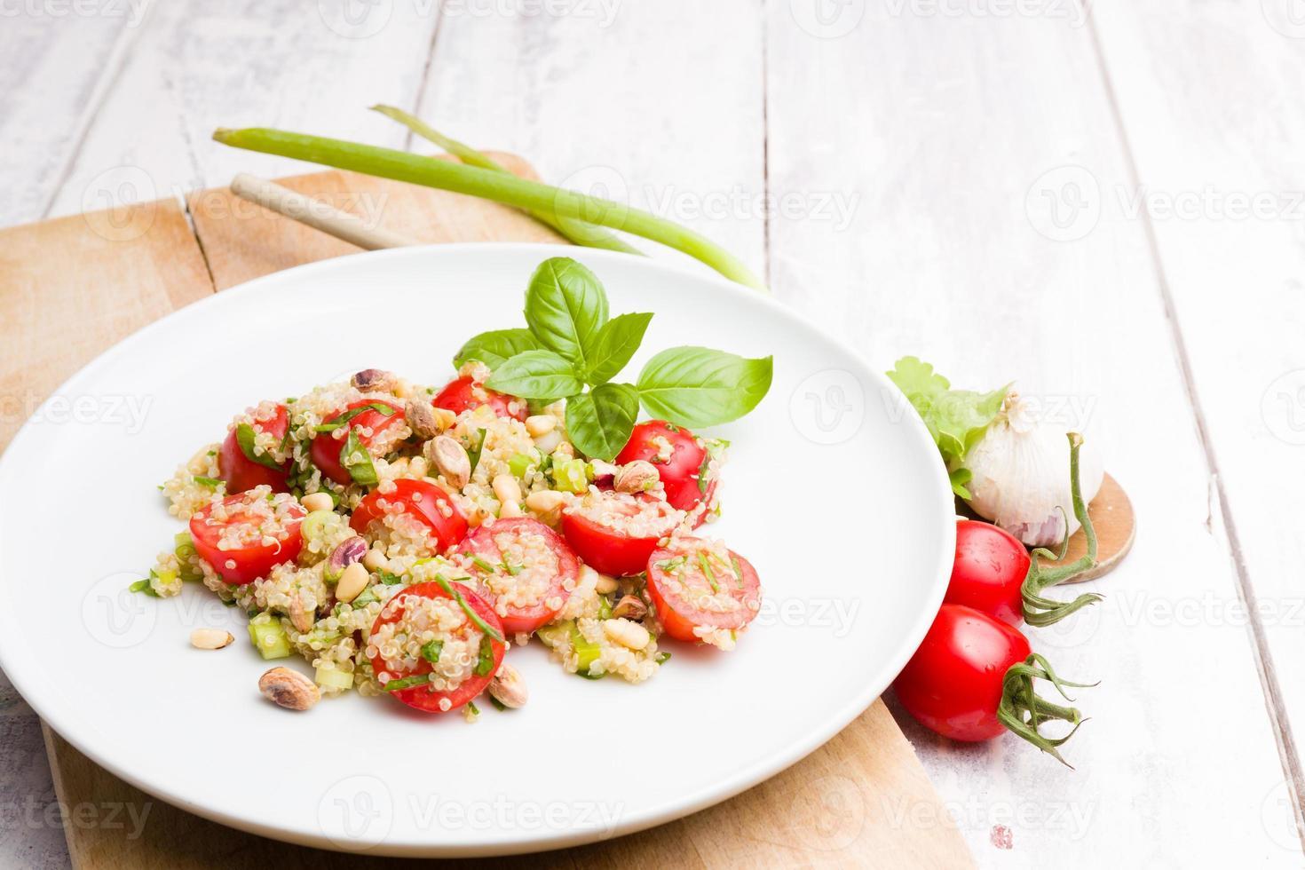 prato de salada vegetariana de quinua em fundo branco de madeira foto
