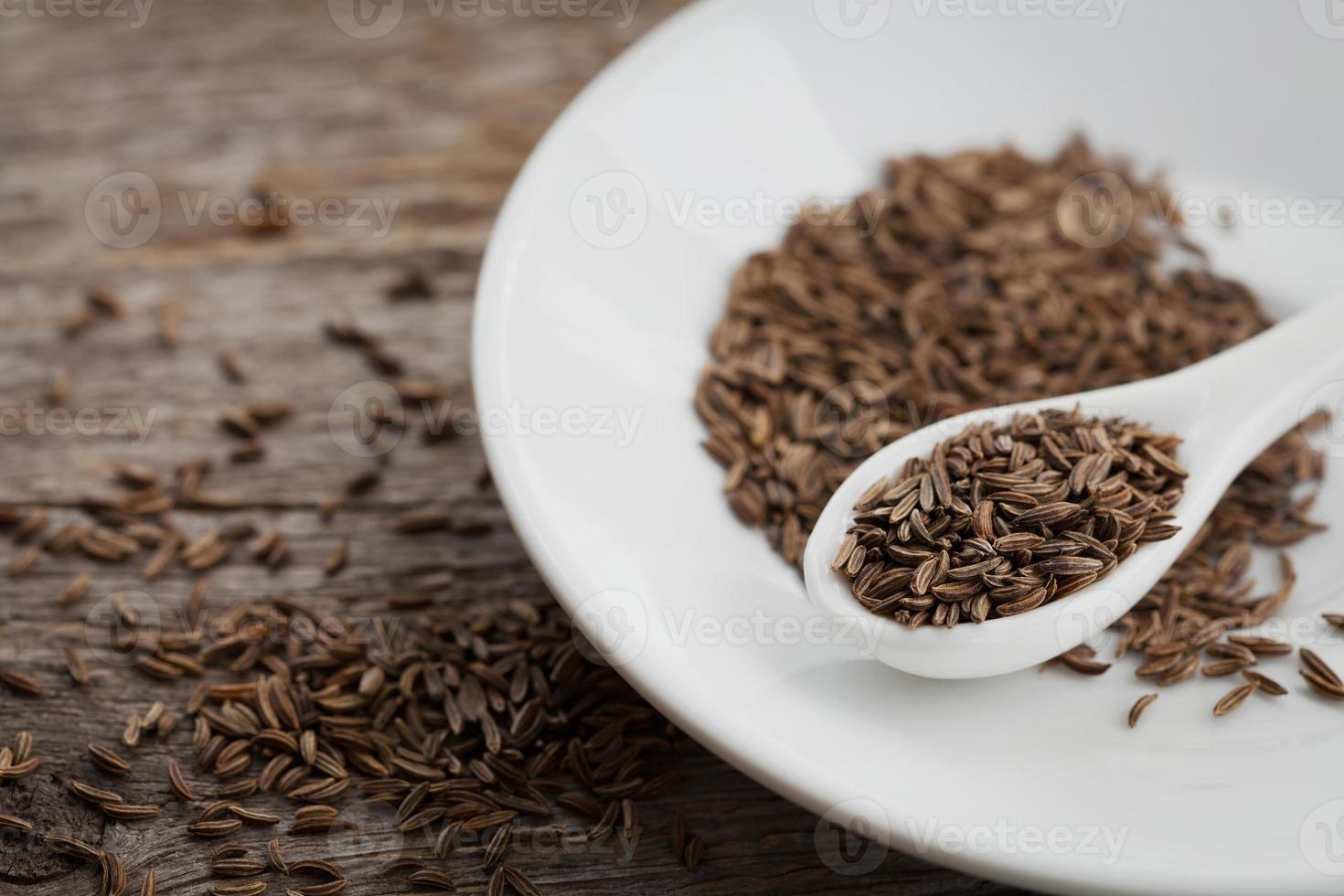sementes de cominho ou cominho na placa de madeira foto