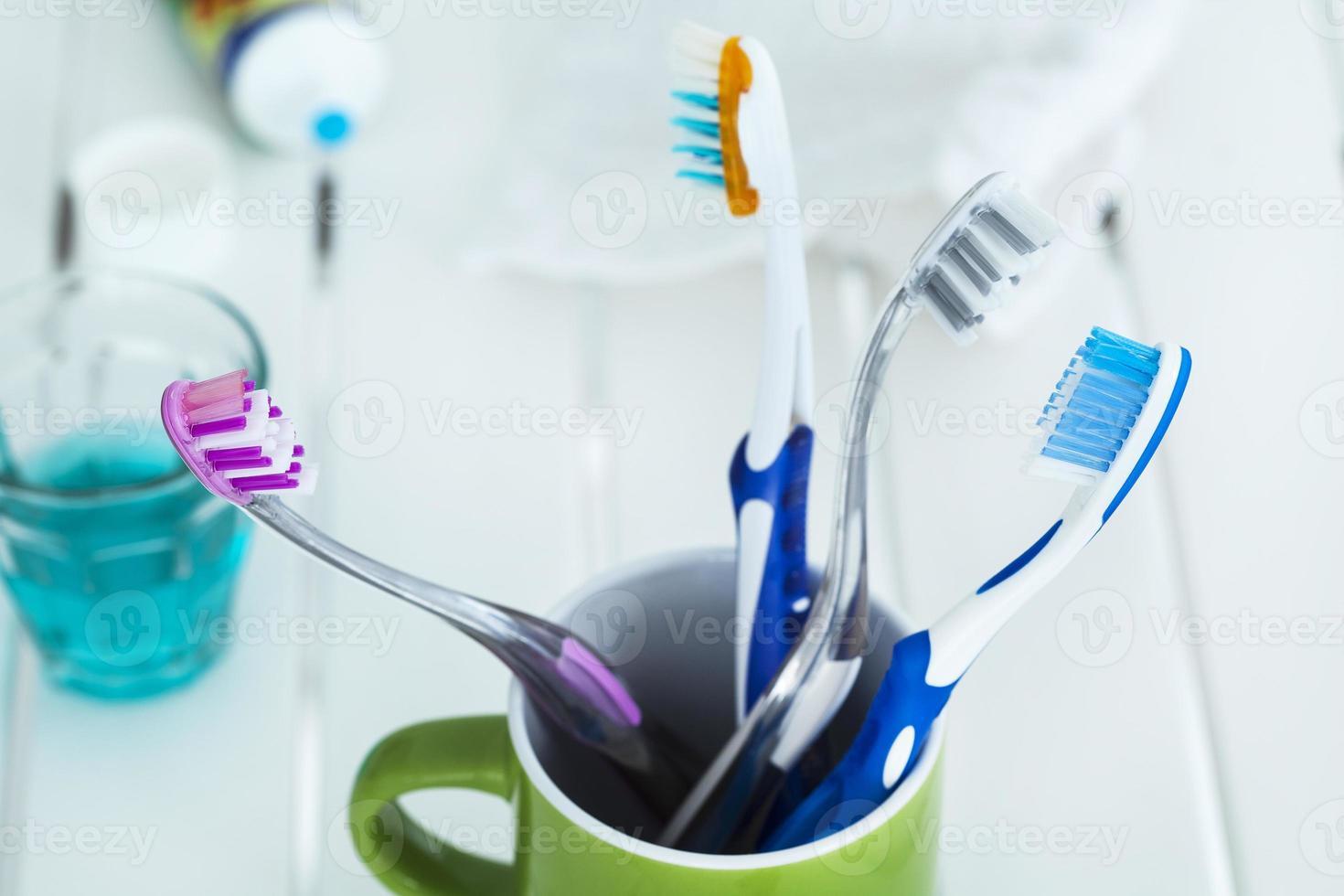 escovas de dente em vidro na mesa foto