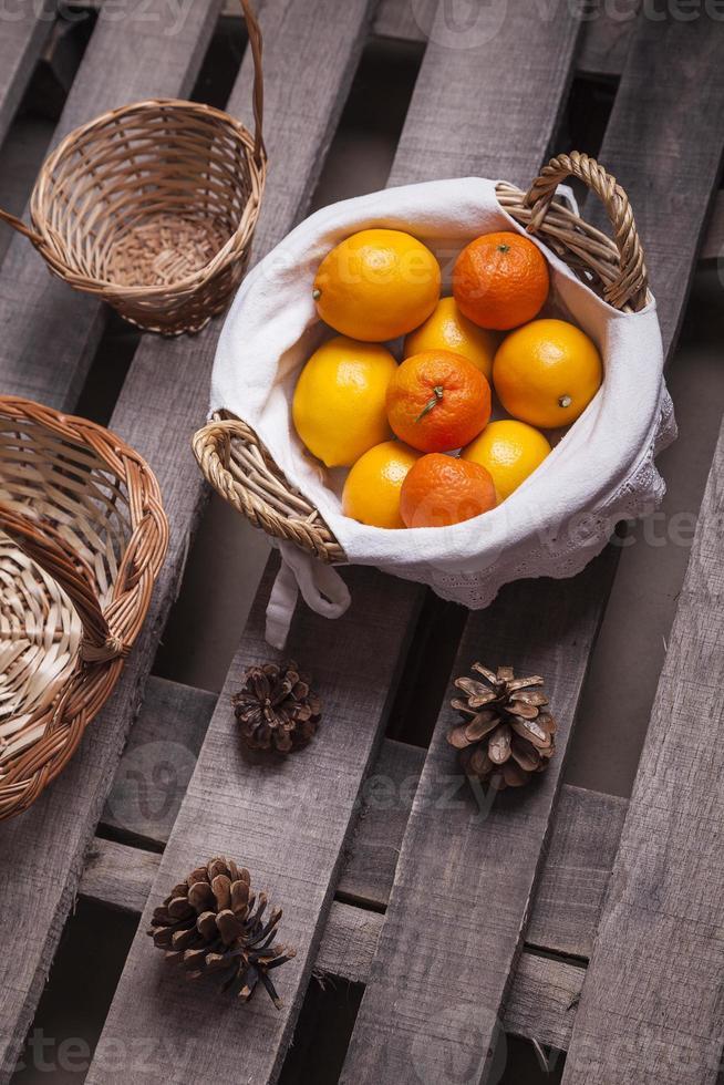 Pilha de tangerinas e limões na cesta de vime foto