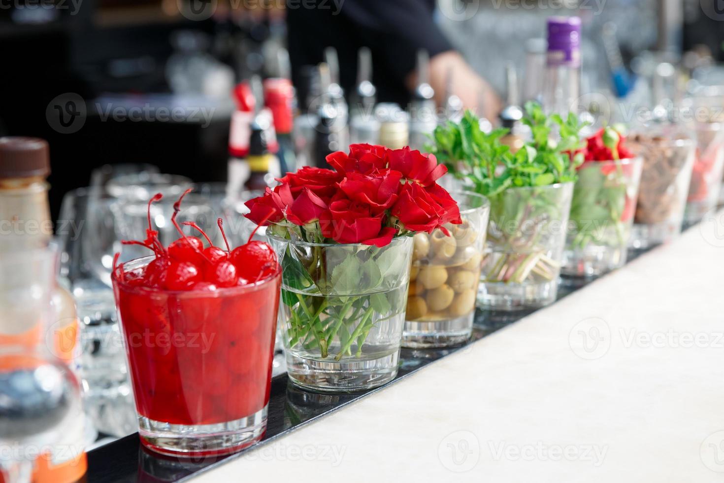 cerejas, ervas e flores no balcão do bar foto