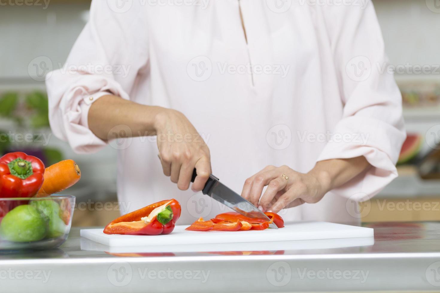 closeup em mulher cortando legumes frescos foto