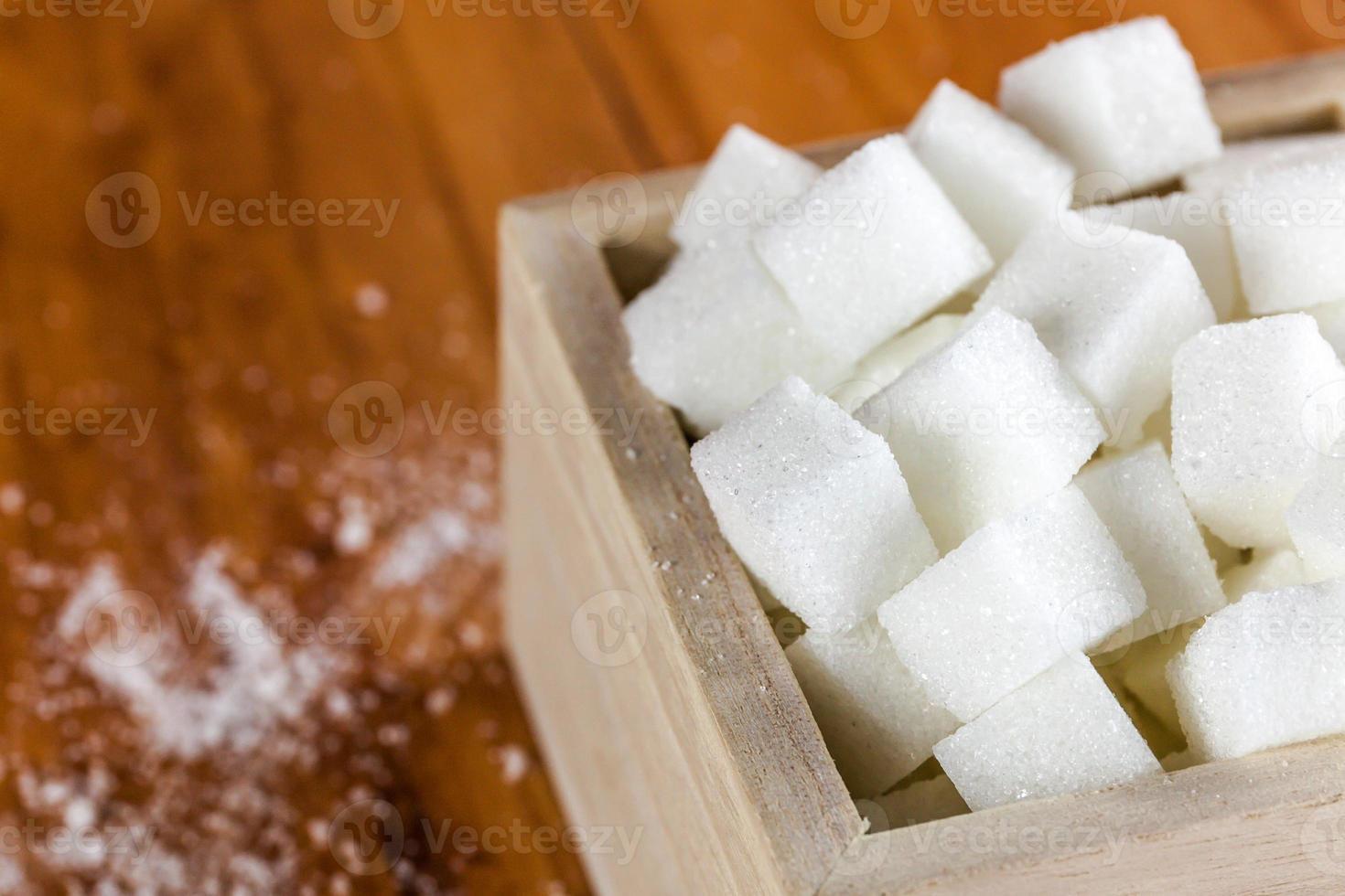 pilha de cubos de açúcar sobre fundo de madeira foto