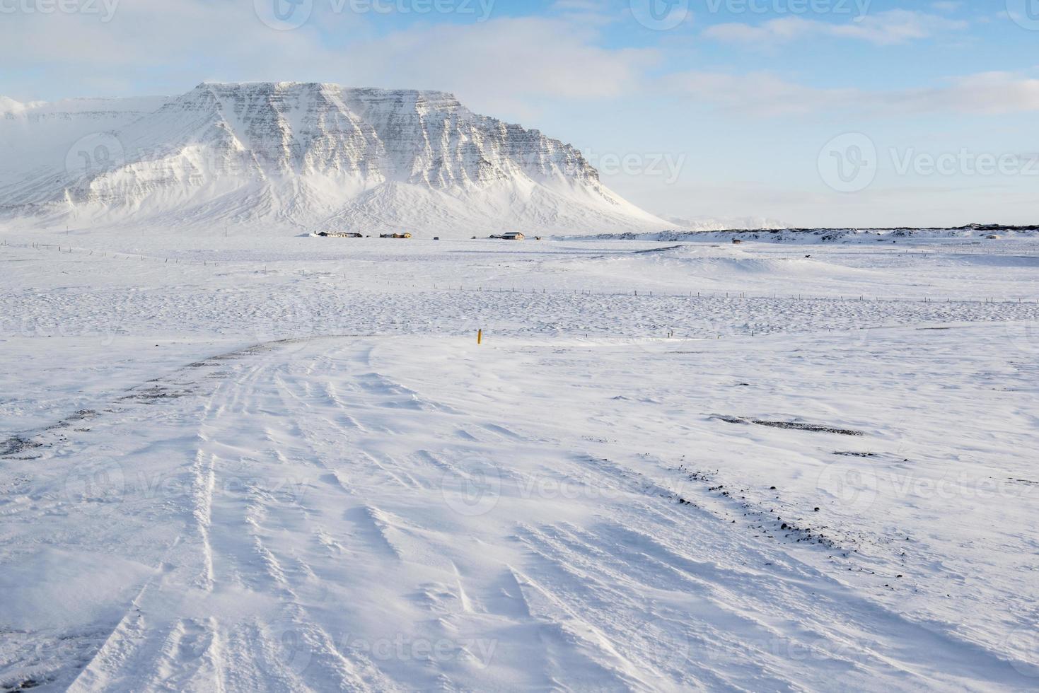 paisagem de inverno com montanhas, neve e pequenas casas de fazenda, Islândia foto