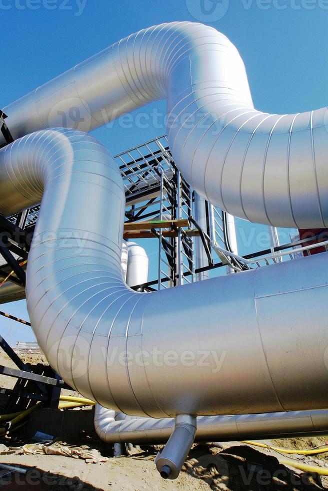 zona industrial, dutos de aço e válvulas contra o céu azul foto