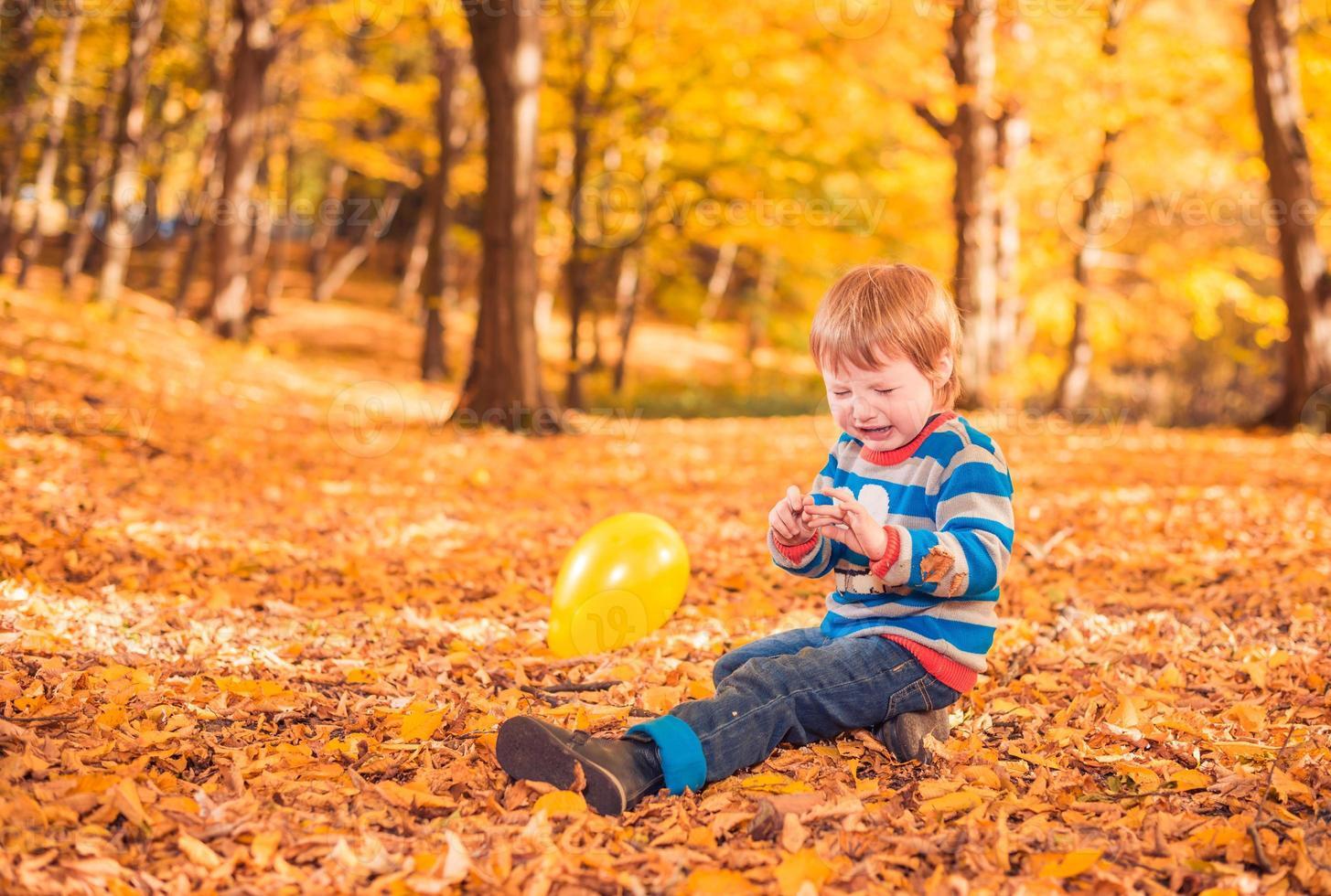 menino chorando na floresta de outono foto