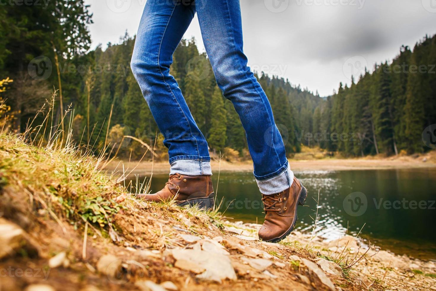 mulher sobe uma colina na floresta foto