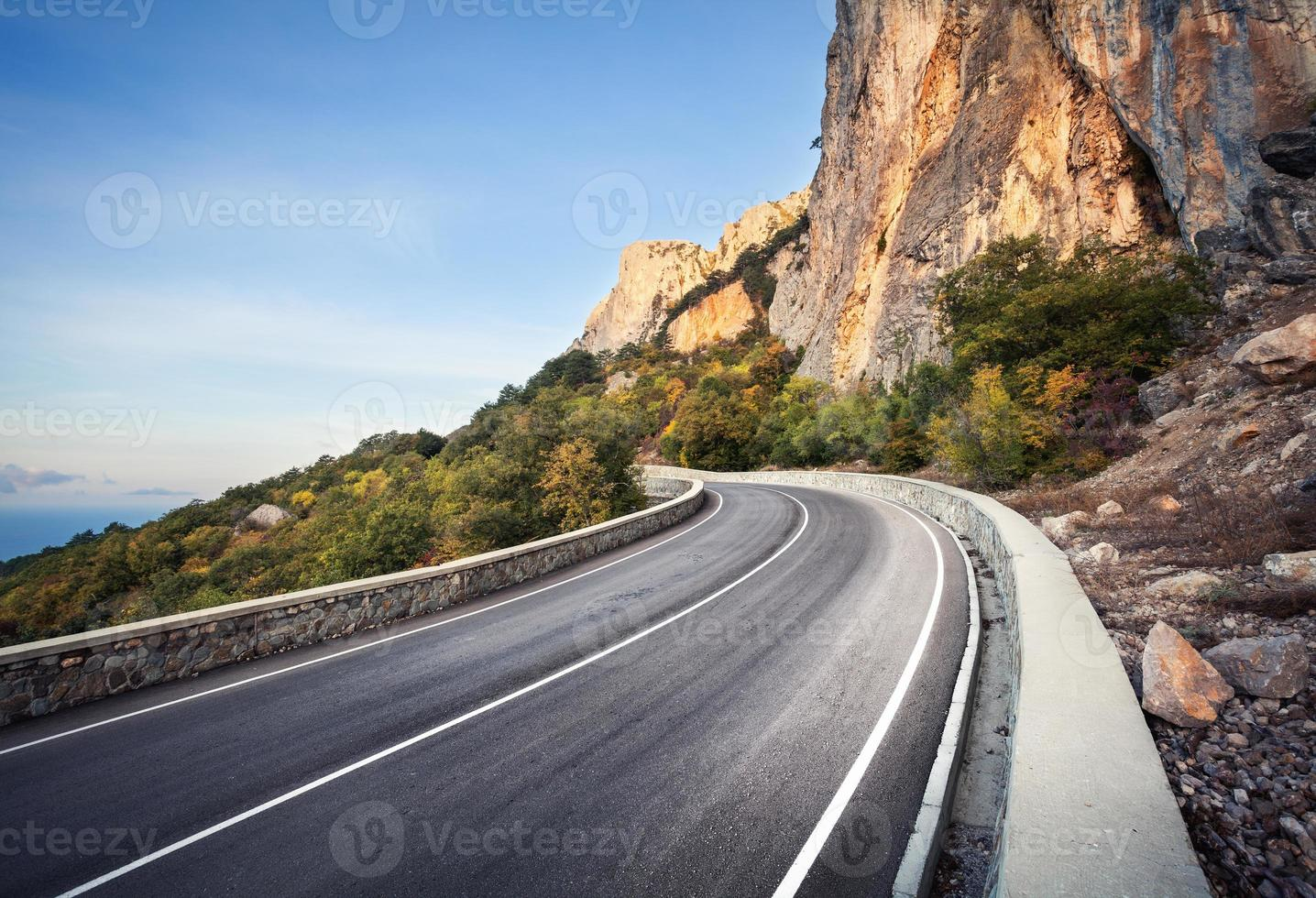 bela estrada de asfalto na floresta de outono ao nascer do sol. montanhas foto