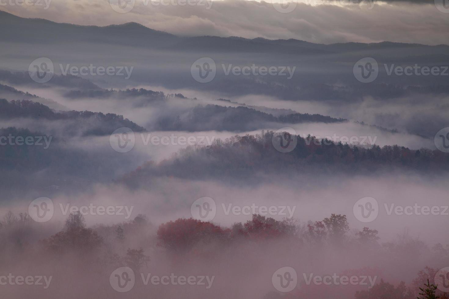 nevoeiro matinal avermelhado sobre montanhas esfumaçadas foto