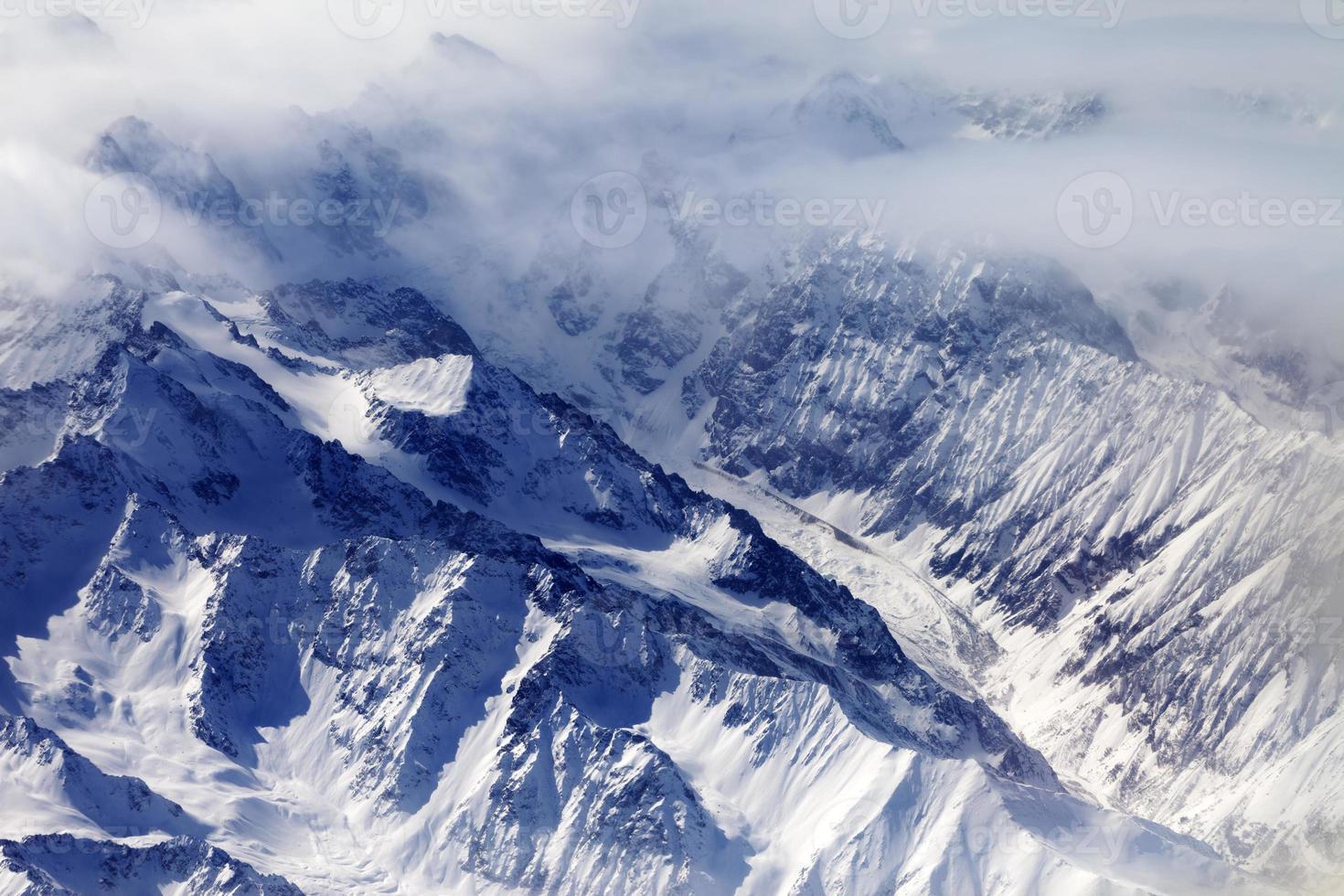 vista superior em montanhas de neve e geleira na névoa foto