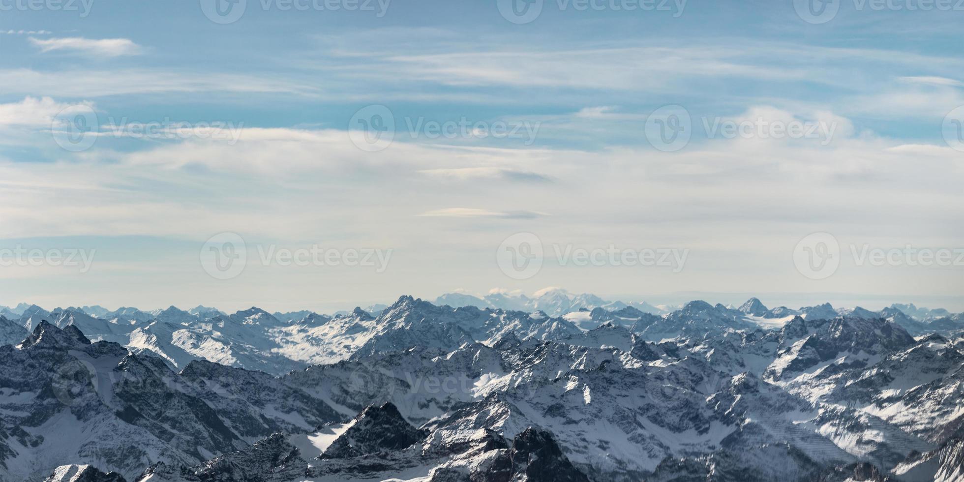 picos de montanhas rochosas nevadas na Áustria com céu azul nublado foto