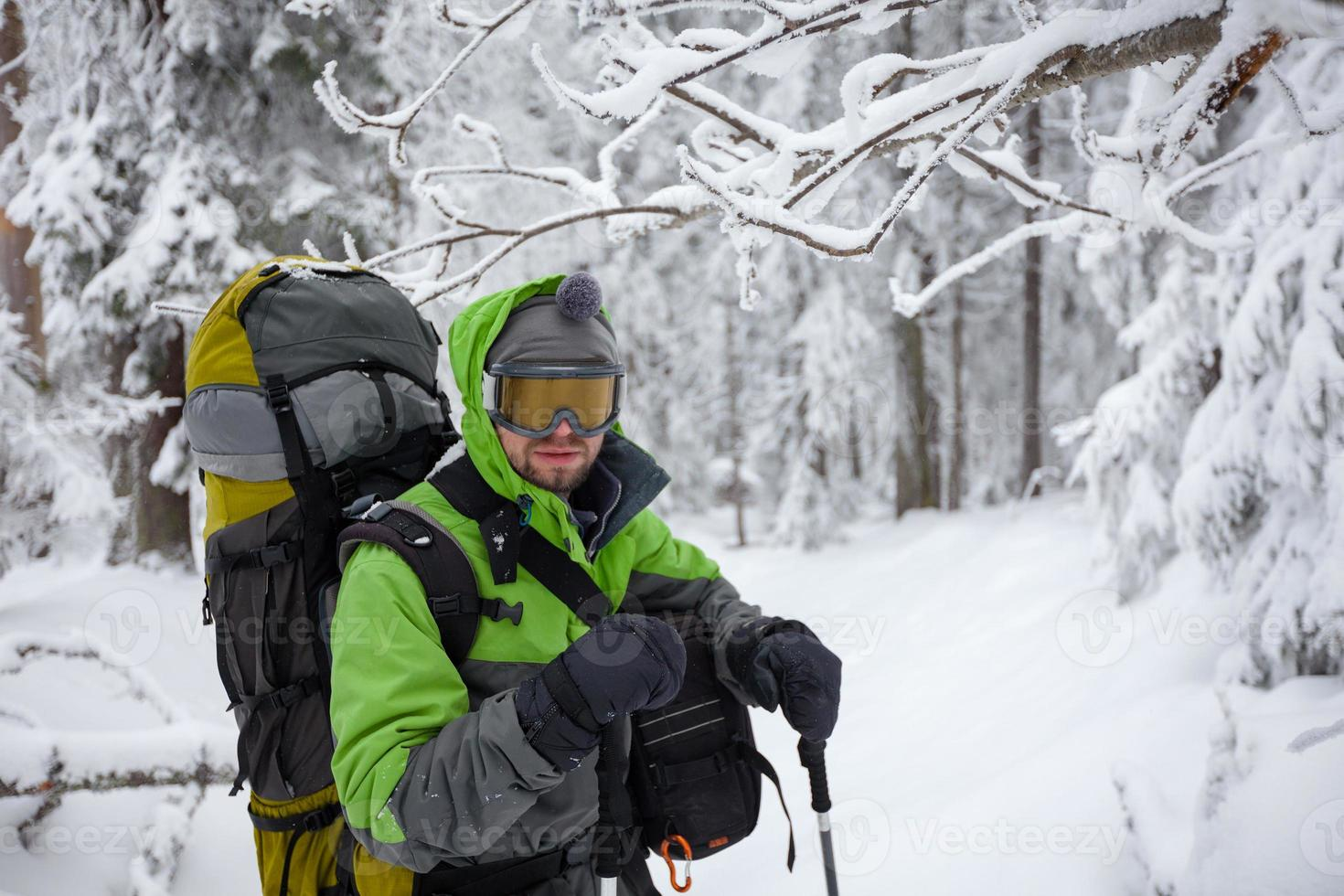 mochileiro posando em montanhas de inverno foto