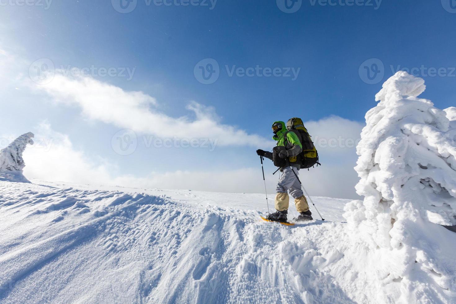 homem mochileiro caminhando nas montanhas de inverno em dia ensolarado foto