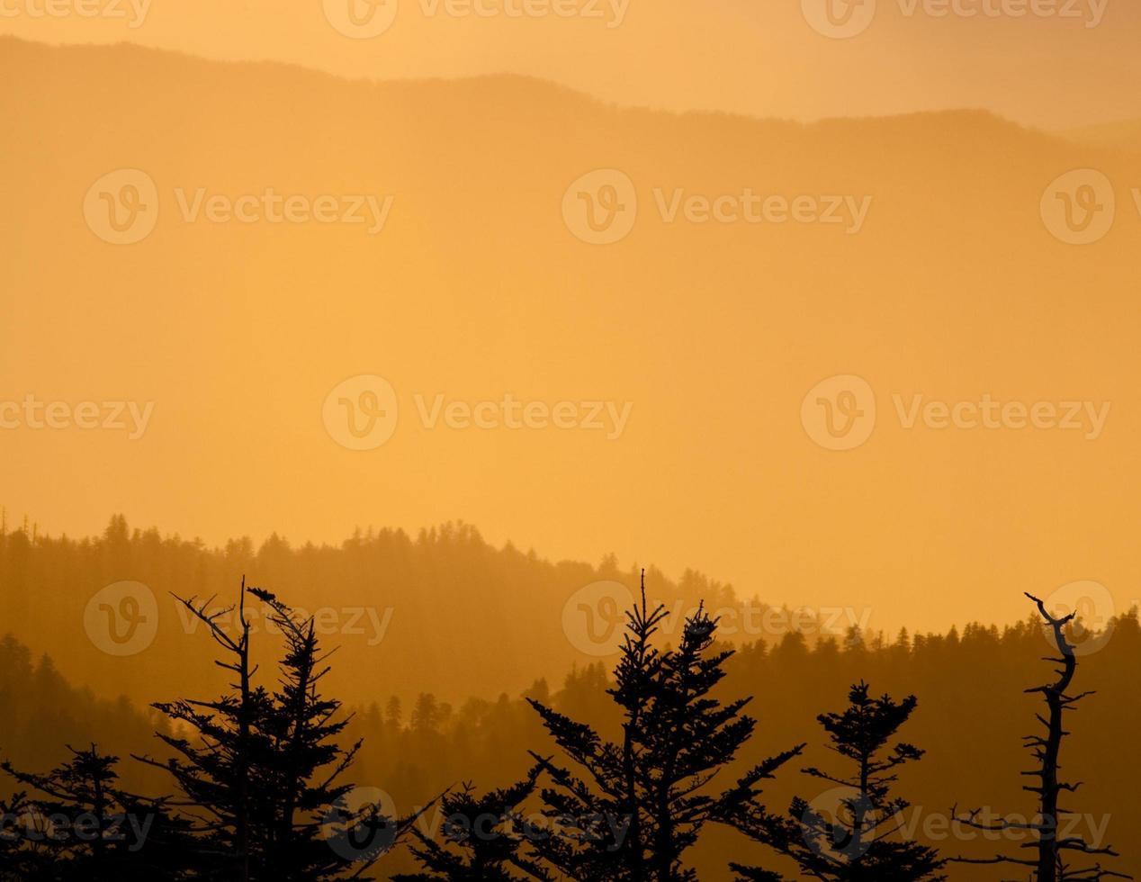 montanhas esfumaçadas ao pôr do sol foto